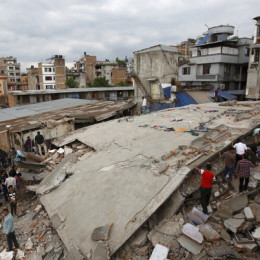 People gather near a collapsed house after a major earthquake in Kathmandu, Nepal April 25, 2015. A shallow earthquake measuring 7.9 magnitude struck west of the ancient Nepali capital of Kathmandu on Saturday, killing more than 100 people, injuring hundreds and leaving a pall over the valley, doctors and witnesses said.  REUTERS/Navesh Chitrakar      TPX IMAGES OF THE DAY      - RTX1A7LL